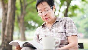 Café bebendo superior asiático do livro de leitura da mulher no parque ensolarado, g Fotografia de Stock Royalty Free