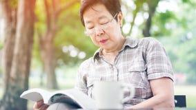 Café bebendo superior asiático do livro de leitura da mulher no parque ensolarado, g Imagens de Stock Royalty Free