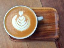 Café blanc plat avec l'art de latte sur la soucoupe en bois Images libres de droits