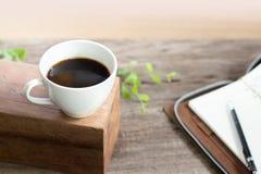 Café blanco de la taza con el cuaderno en la tabla superior de madera Fotos de archivo libres de regalías
