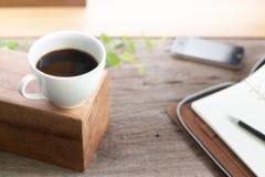 Café blanco de la taza con el cuaderno en la tabla superior de madera Foto de archivo libre de regalías