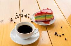 Café blanco de la taza con la torta del crepé del color en el foco de madera de la tabla en el cr Fotografía de archivo