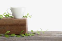 Café blanco de la taza en la tabla superior de madera aislada Imagen de archivo libre de regalías