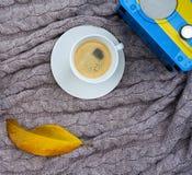 Café blanco de la taza y receptor de radio azul amarillo y hoja amarilla caida en la tela escocesa rosada gris de lana caliente M foto de archivo libre de regalías