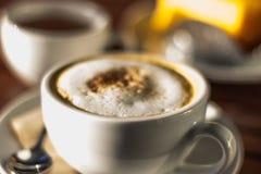 Café blanco del macchiato del choc en la taza blanca con té y la torta anaranjada Fotos de archivo