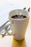 Café, bolígrafo y periódico calientes Imagen de archivo