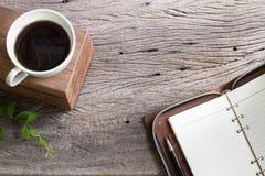 Café branco do copo com o livro de nota na tabela superior de madeira Foto de Stock Royalty Free