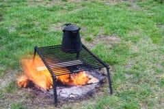 Café brassant au-dessus d'un feu ouvert de camp Photo stock