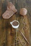 Café, calcetín de lana y el hacer punto en una tabla imágenes de archivo libres de regalías