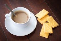 Café caliente con las galletas en la tabla de madera Foto de archivo