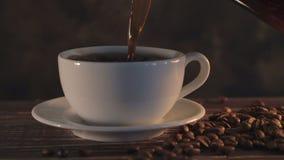 Café caliente con los granos de café en la tabla de madera almacen de video