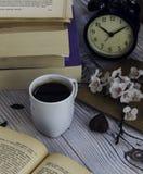 Café caliente con los libros viejos y el despertador Fotografía de archivo libre de regalías