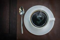 Café caliente con reflejo de la muestra del dinero en el top, concepto del negocio Fotos de archivo