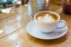Café caliente del arte del Latte en la tabla de madera Fotos de archivo libres de regalías