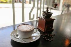 Café caliente del latte en arte de la forma de hoja con la máquina griding de la mano adentro Foto de archivo libre de regalías