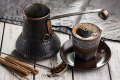 Café caliente en la taza turca tradicional, turka de cobre del cezve, especias en la tabla de madera vieja con la servilleta Fotos de archivo libres de regalías