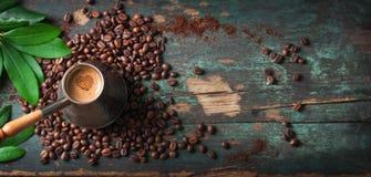 Café caliente en una cafetera o un turco en un fondo de madera con las hojas y las habas del café, horizontales con el espacio de Imagen de archivo