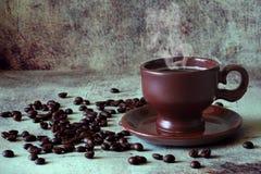 Café caliente fragante en una taza hermosa de la arcilla entre los granos de café dispersados imagen de archivo