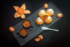 Café caliente fresco en las tazas de cerámica, la mandarina madura y el postre dulce – profiterole imagen de archivo libre de regalías