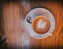 Café caliente italiano del capuchino con espuma en forma de corazón en la tabla de madera Imagen de archivo libre de regalías