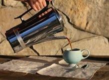 Café caliente que es vertido en la taza Fotografía de archivo