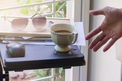 Café caliente sucio en la tabla del ordenador portátil Foto de archivo