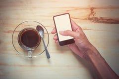 Café caliente y mano que sostienen el teléfono móvil fotografía de archivo libre de regalías