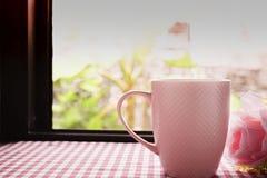 Café caliente y rosas rosadas dulces en la tabla Imagen de archivo libre de regalías