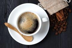 Café chaud avec de la cannelle, une cuillère en bois et un sac des grains de café Photo stock