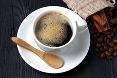 Café chaud avec de la cannelle, une cuillère en bois et un sac des grains de café Photos stock