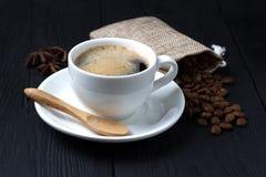Café chaud avec l'anis, une cuillère en bois et un sac des grains de café Photo stock
