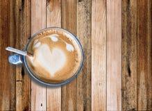 Café chaud avec l'art de mousse de lait, sur le vieux bureau en bois Photographie stock