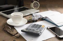 Café chaud avec le téléphone portable de carnet d'ordinateur sur la table en bois Image libre de droits