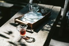 Café chaud d'égouttement dans le verre à boire sur la table en bois avec la lumière du soleil dure image libre de droits