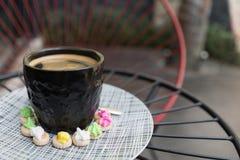 Café chaud d'Americano avec le dessus de crema dans un surr en verre noir chic Photos libres de droits