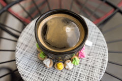 Café chaud d'Americano avec le dessus de crema dans un surr en verre noir chic Images libres de droits