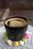 Café chaud d'Americano avec le dessus de crema dans un surr en verre noir chic Photos stock