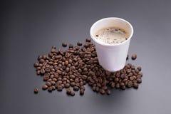 Café chaud d'americano dans la tasse de papier de café et de grains de café dessus Images libres de droits