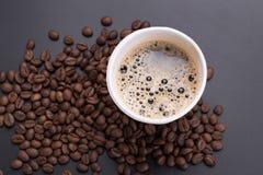 Café chaud d'americano dans la tasse de papier de café et de grains de café dessus Photo libre de droits