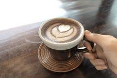 Café chaud d'amour avec de la fumée par art de latte sur une tasse photos stock
