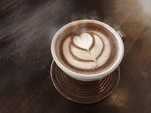 Café chaud d'amour avec de la fumée par art de latte sur une tasse photographie stock libre de droits