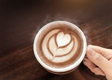 Café chaud d'amour avec de la fumée par art de latte sur une tasse photo stock