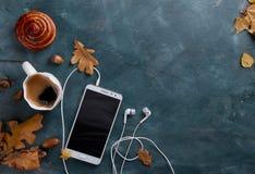 Café chaud dans la tasse et le petit pain, le téléphone portable avec des écouteurs et l'autu Photos libres de droits