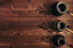 Café chaud dans le cezve turc minable aimable différent de pots avec l'espace de copie sur le vieux fond brun de conseil en bois, photos stock