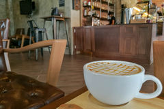Café chaud de crème de caramel dans la tasse blanche avec le fond de café Photos stock