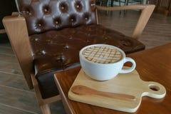 Café chaud de crème de caramel dans la tasse blanche avec le fond de café Images stock
