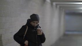 Café chaud de jolies boissons de femme dans le tunnel, attendant quelqu'un, retard, hiver banque de vidéos