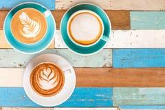 Café chaud de la vue trois supérieure dans la tasse et sur la table en bois Photographie stock