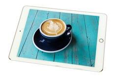 Café chaud de Latte d'art dans une tasse sur le tabl en bois bleu dans le comprimé sur W Image stock