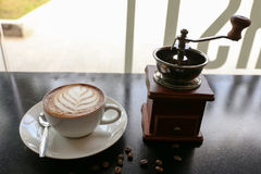 Café chaud de latte dans l'art de forme de feuille avec la machine de meulage de main dans un café Photos stock